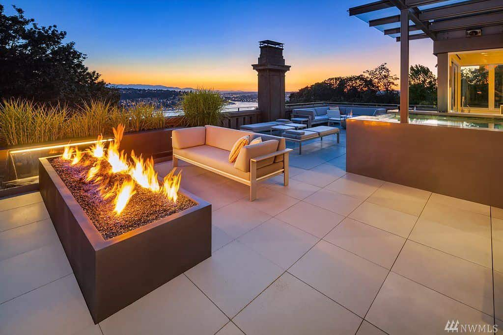 Massive patio with two lounge areas and two fire pits. One gas fire feature very large (rectangle).