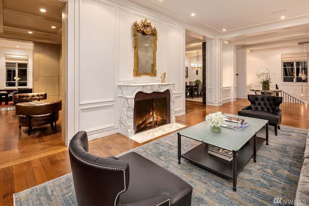 Sitting area next to fireplace in formal living room. White walls, light hardwood and area rug.