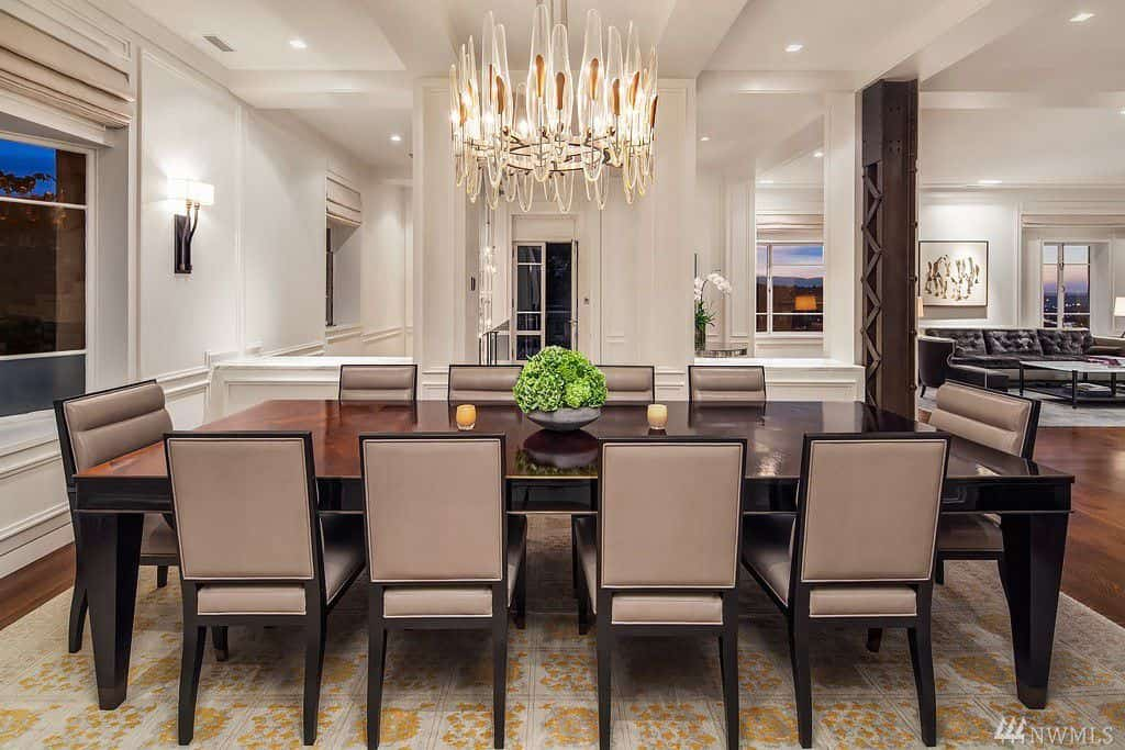Formal dining room with seating for 10 people and gorgeous chandelier above dining table.