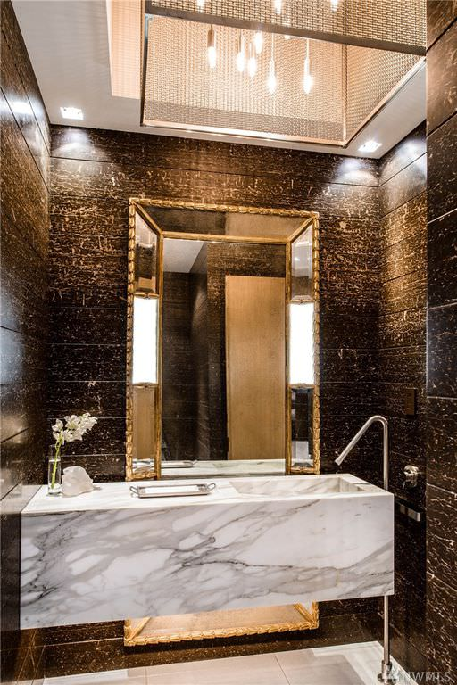 Glamorous powder room with marble vanity, dark brown walls and large mirror.