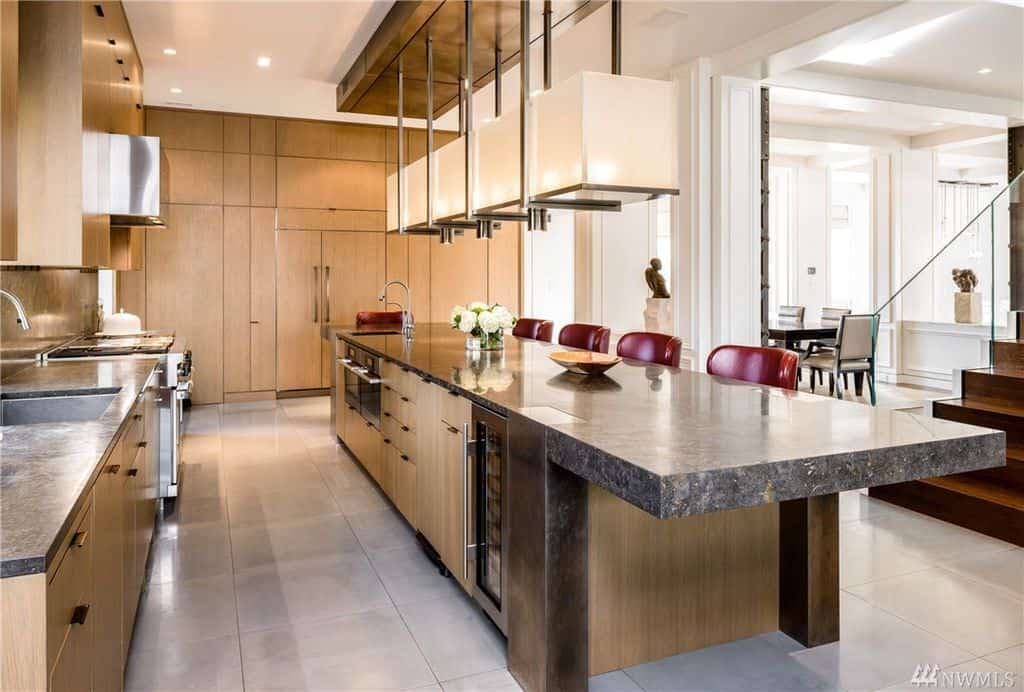 This modern style kitchen offers a long center island featuring a granite countertop along with red bar stools lighted by stunning pendant lights. The walnut cabinetry looks good with the kitchen style as well.