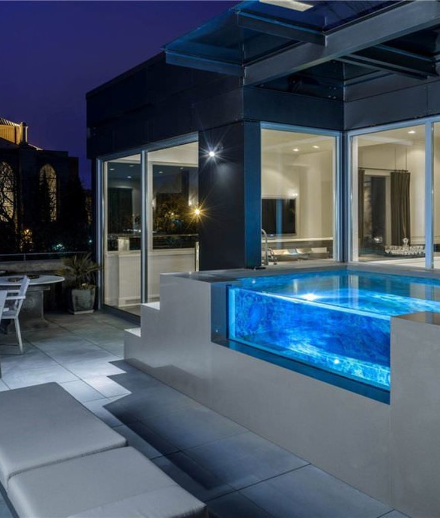Very cool small glass-sided swimming pool on patio.