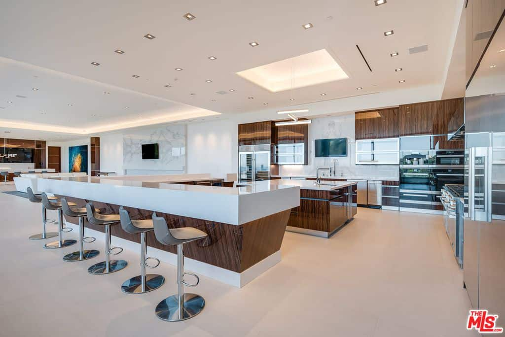 This contemporary kitchen is stunningly beautiful. The smooth white center island with laminated details offers a six-seat breakfast bar while the scattered ceiling lights brighten the area.