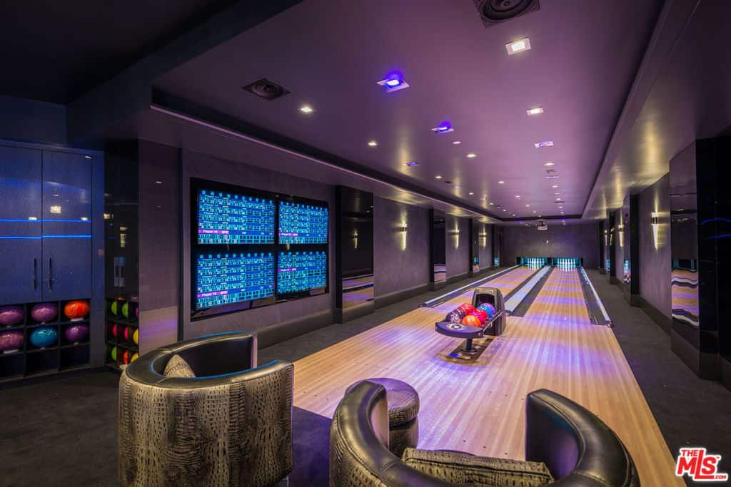This home boasts a bowling alley with elegant seats and black carpet flooring matching the black walls and a stunning tray ceiling.