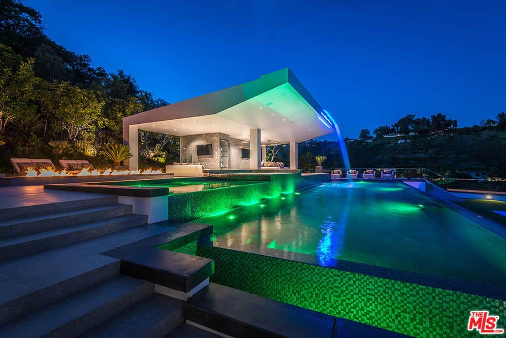 Glass-faced swimming pool with green night lighting