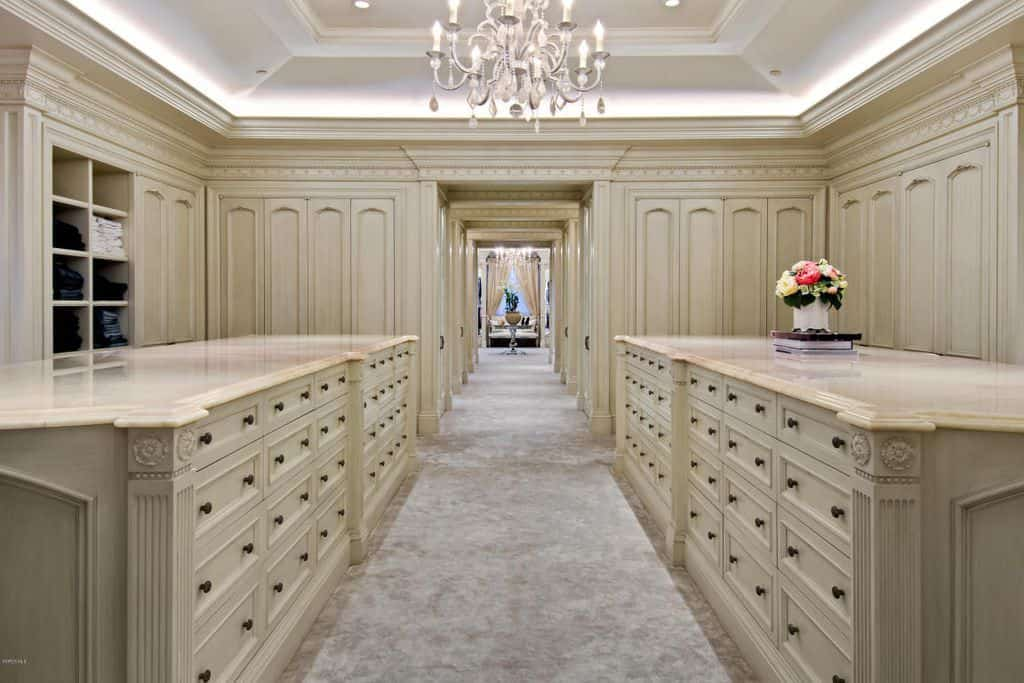 Large walk-in closet with multiple cabinets and shelves along with the beautiful carpet flooring and tray ceiling lighted by a glamorous chandelier.