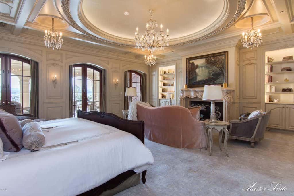 Luxury primary bedroom with a wooden bed and seating area by the fireplace illuminated by fancy crystal chandeliers that hung from the ornate round tray ceiling.