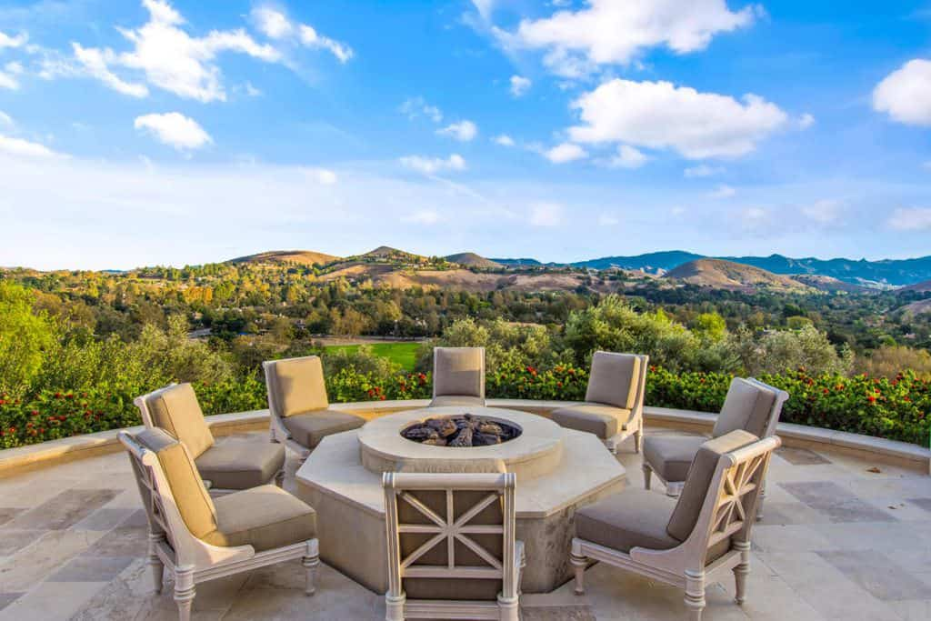 This patio boasting a modern set of seats surrounds a round fire pit while overlooking the beautiful nature.