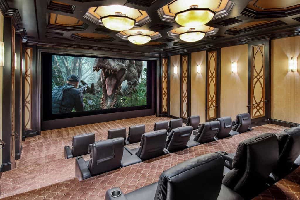 Large home theater with stylish walls and stunning ceiling lighted by a lovely set of wall lights and recessed lighting.