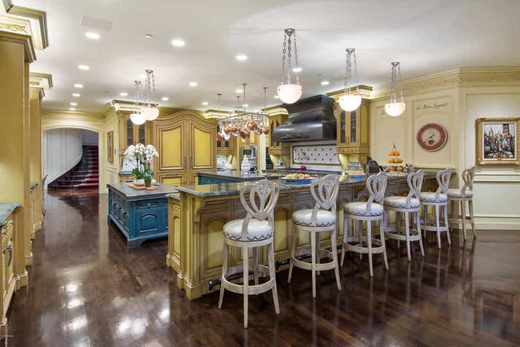 This Mediterranean kitchen offers a long center island with a six-seat breakfast bar lighted by cute pendant lights. The hardwood flooring looks stunning along with the yellow and blue cabinetry.