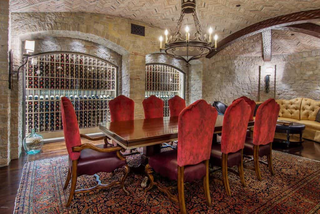 Wine cellar features custom wine rack in an arched brick wall along with a wooden tasting table with red chairs that sit on a huge vintage rug. An iron wrought candle chandelier adds a timeless look in the room.