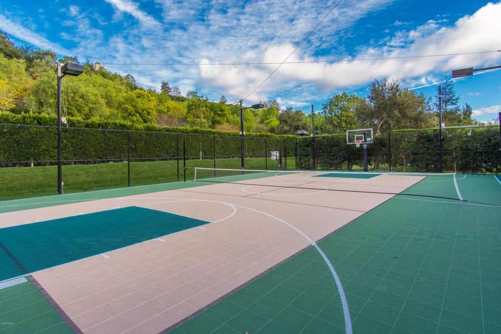 Gorgeous tennis and basketball court in backyard.