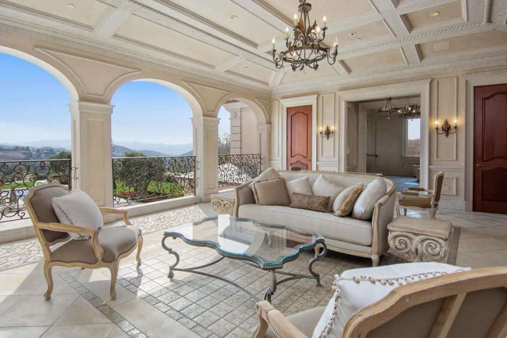 Balcony-type formal living room with a classy set of seats and a glass top center table lighted by a gorgeous chandelier hanging from the coffered ceiling.