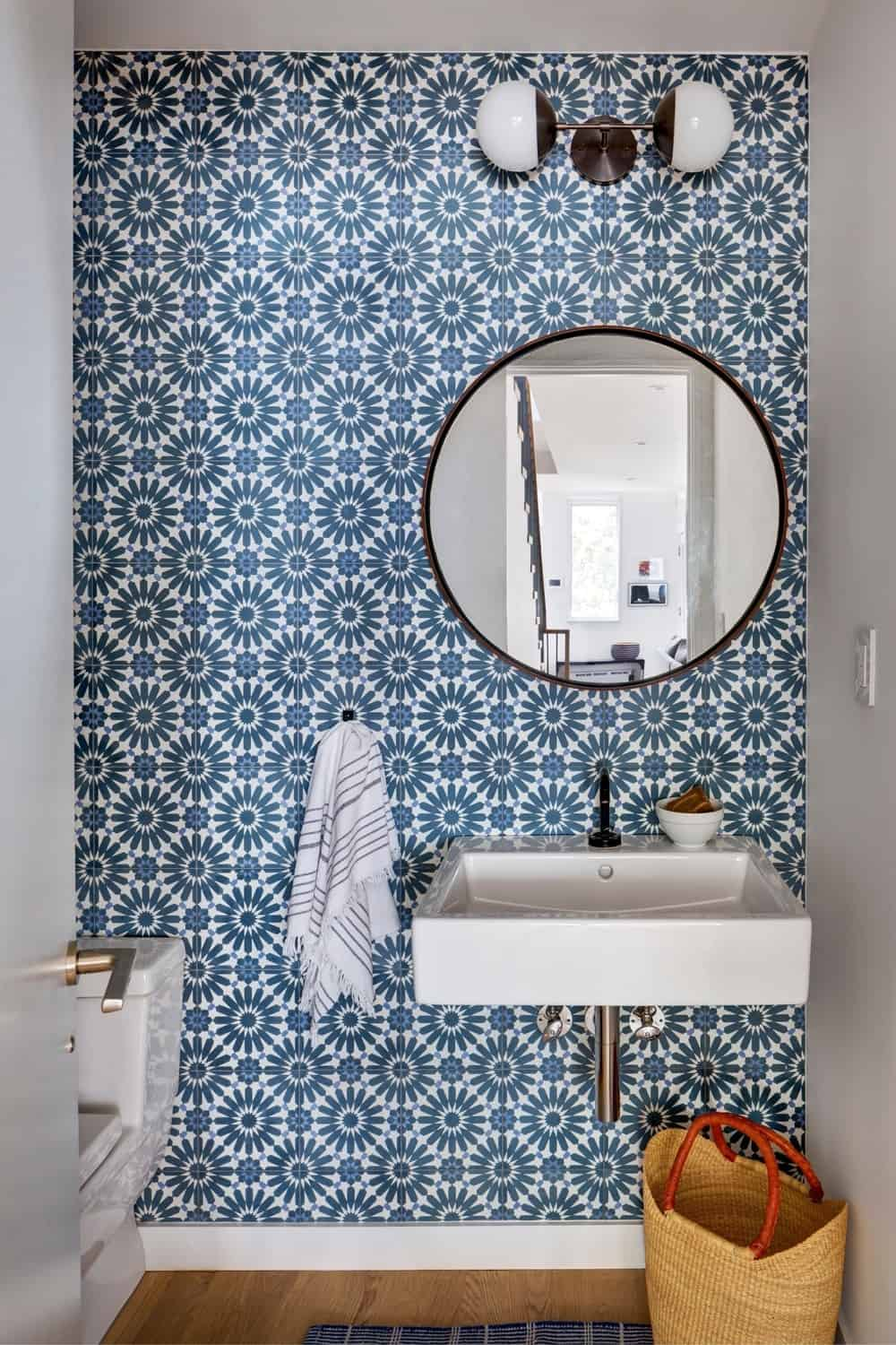 Small bathroom with blue stylish wall and floating vanity sink. Photo Credit: Francis Dzikowski/OTTO