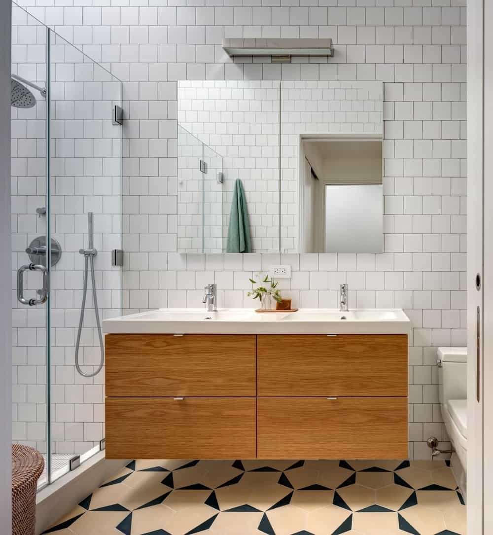 Contemporary primary bathroom with attractive tiles flooring. The room offers a double sink and a walk-in shower room.