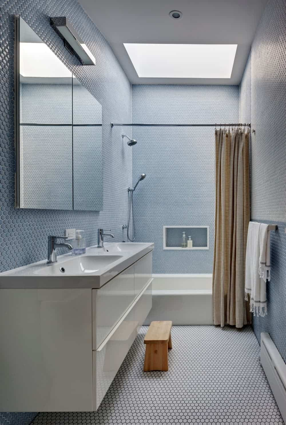 Contemporary bathroom with a tub and shower combo along with a double sink and skylight. Photo Credit: Francis Dzikowski/OTTO