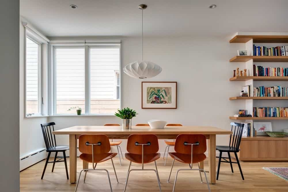 Rectangular dining table set with white walls and pendant lighting along with vinyl flooring and glass windows. Photo Credit: Francis Dzikowski/OTTO