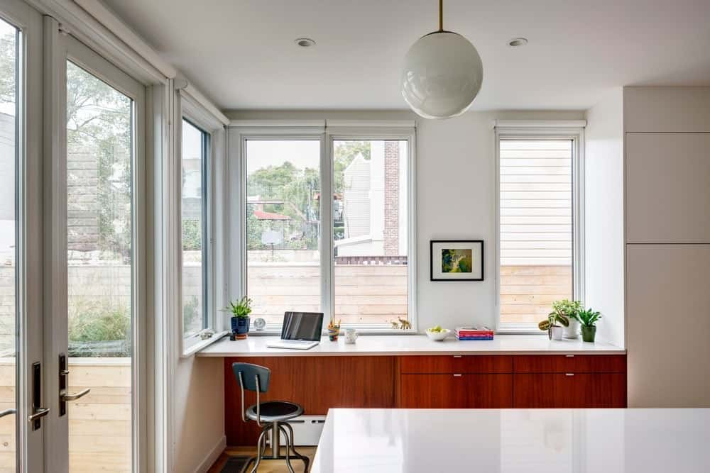 Home office with built-in desk and pendant lighting along with glass windows and door. Photo Credit: Francis Dzikowski/OTTO