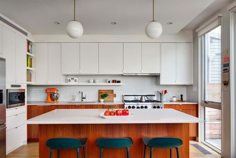 L-shape kitchen with white countertops and cabinets along with a breakfast bar lighted by pendant lights. Photo Credit: Francis Dzikowski/OTTO