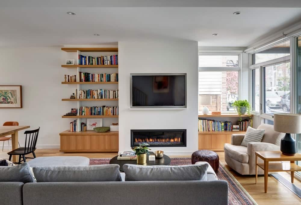 Contemporary family room with built-in shelving and vinyl flooring along with TV on wall and a fireplace. Photo Credit: Francis Dzikowski/OTTO