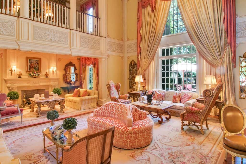 A mansion featuring a majestic large formal living room featuring lovely seats and stunning window curtains.