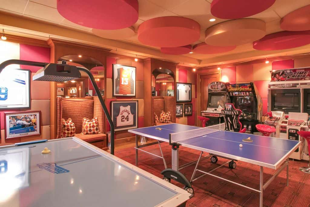 This game room boasts multiple arcade games and a table tennis set surrounded by stylish walls that match the ceiling.