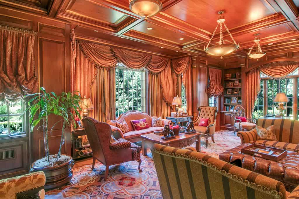 A glamorous formal living room featuring an elegant coffered ceiling and classy set of seats and window curtains.