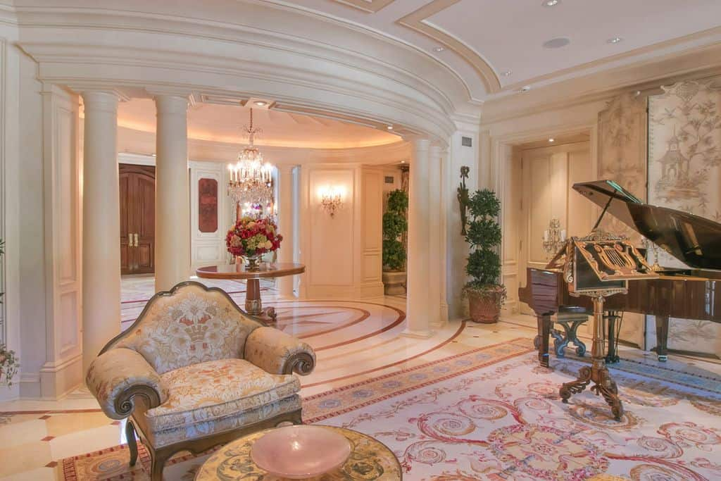 Classy large foyer featuring a lovely rug set on a beautiful flooring. The club chair looks elegant.