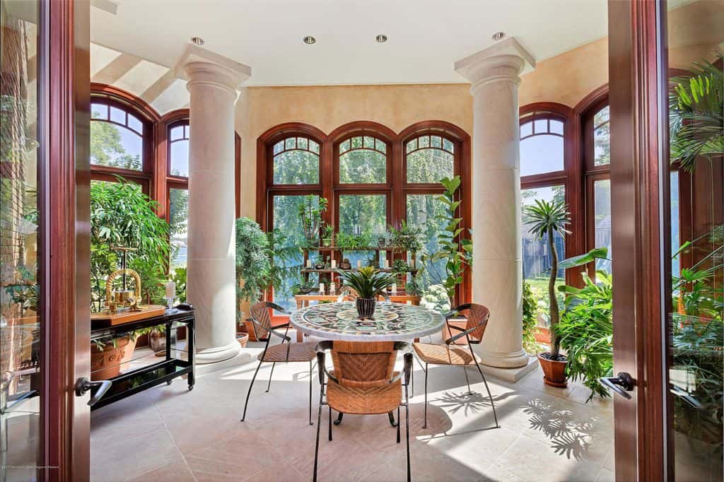 Sunroom for dining with arched windows and columns.