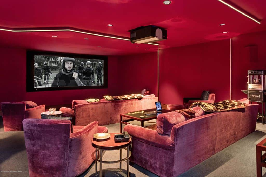 Burgundy color media room with projector screen and stadium seating.