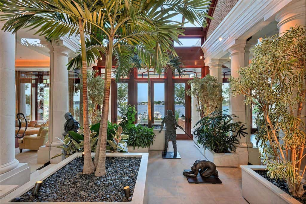 Home foyer with trees and glass roof.