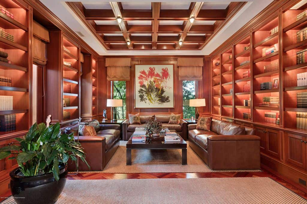 A large home library featuring stunning bookshelves and elegant brown leather seats. The coffered ceiling and the reddish hardwood flooring are so perfect together.