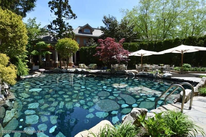 A gorgeous stone swimming pool with clear water and stainless steel handrails. It offers plenty of seats with umbrella shades.