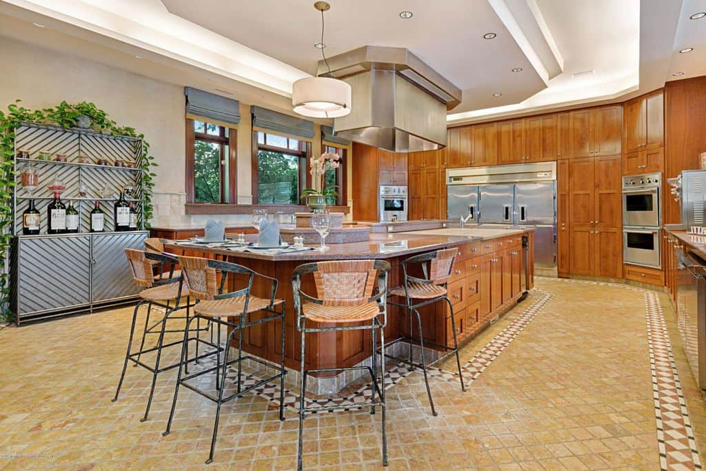 This kitchen offers a wide space along with a large center island featuring a cozy breakfast  bar. The walnut cabinets add beauty to the already stunning kitchen.