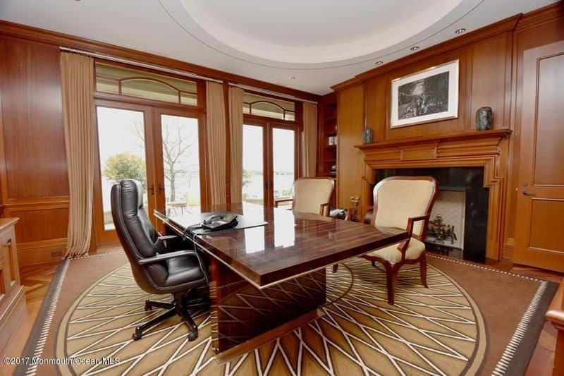 Home office with huge wood desk and fireplace