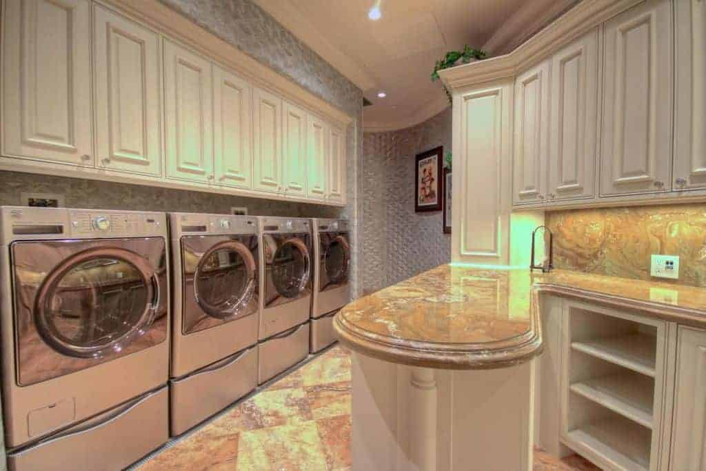 Laundry room with 2 washers and 2 dryers, cabinetry and counter space.