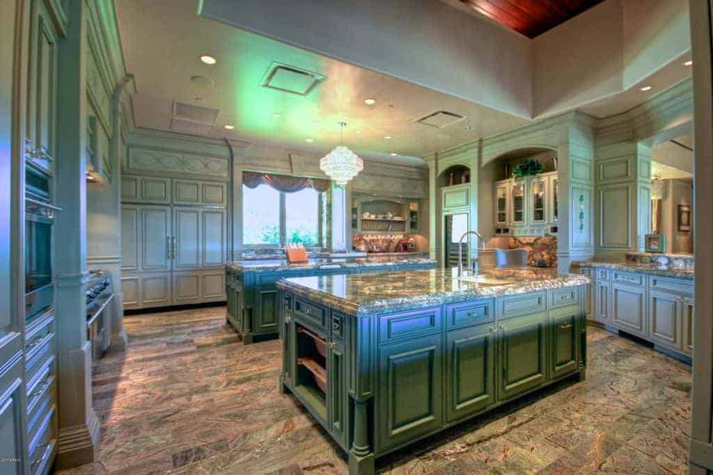 Green kitchen with two islands and hardwood flooring.