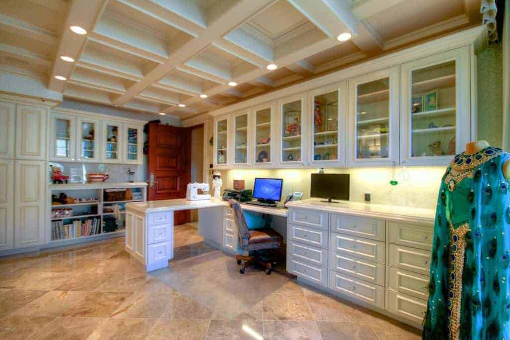 Spacious home office with built-in desk and cabinets.