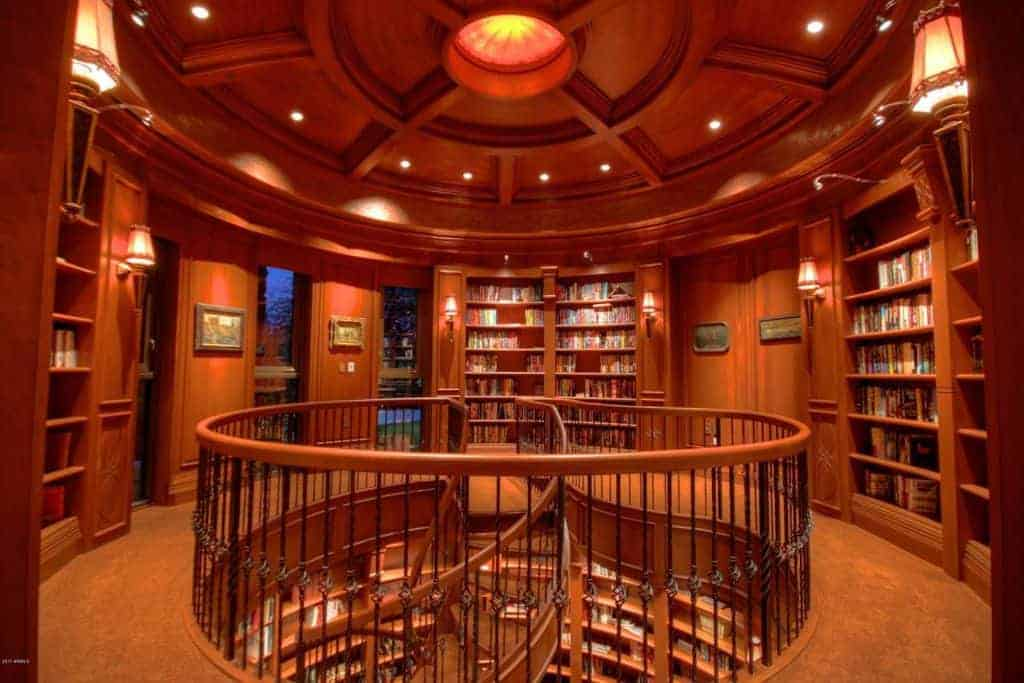 Upper floor of home library with circular stairs leading to first floor of library.