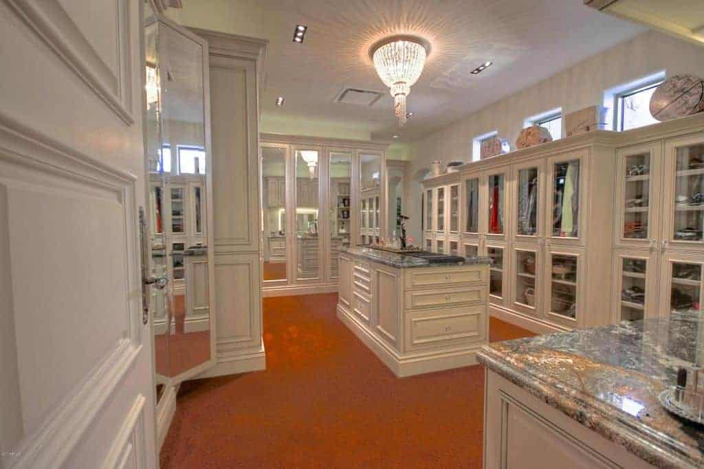 Large bedroom closet featuring classy granite counters and a large center island. The cabinetry matches the white walls and ceiling lighted by a beautiful ceiling light.