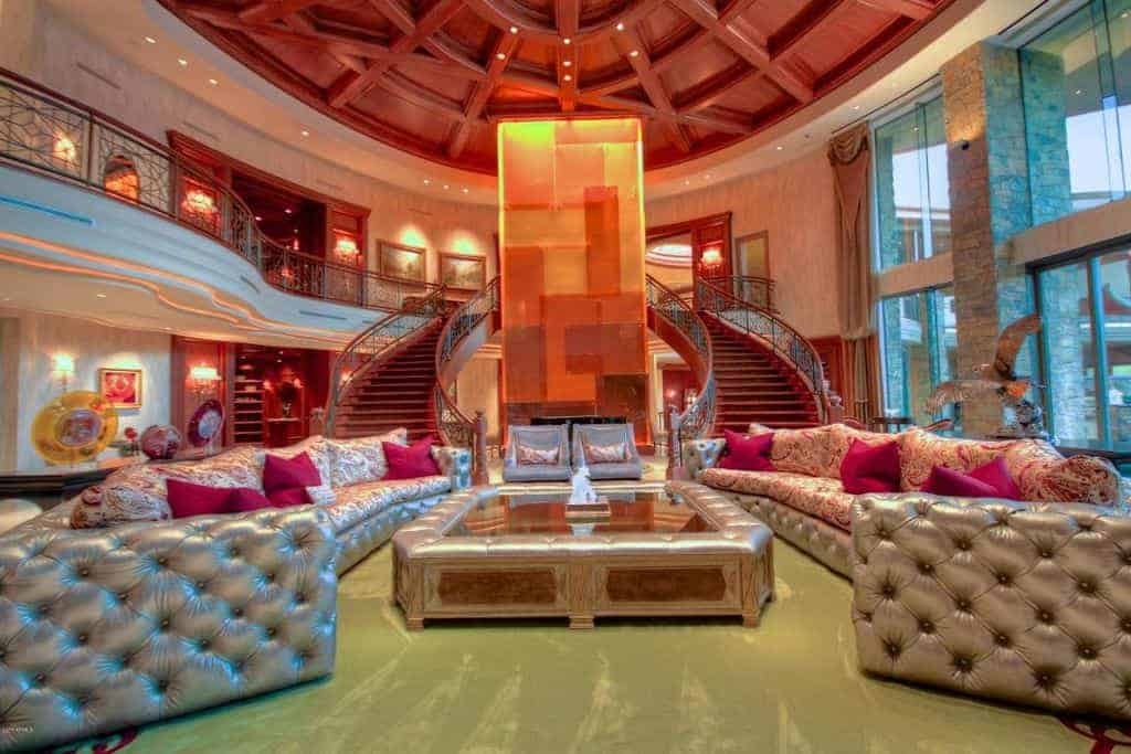 A jaw-dropping large formal living room with an elegant towering ceiling and sofa set along with the smooth sparkling floors. The grand foyer can be seen in the background.