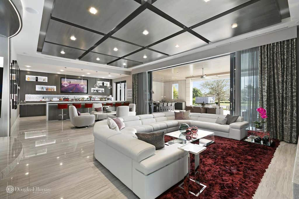 Huge family room and home bar in contemporary style. Large u-shaped white leather sectional sofa.