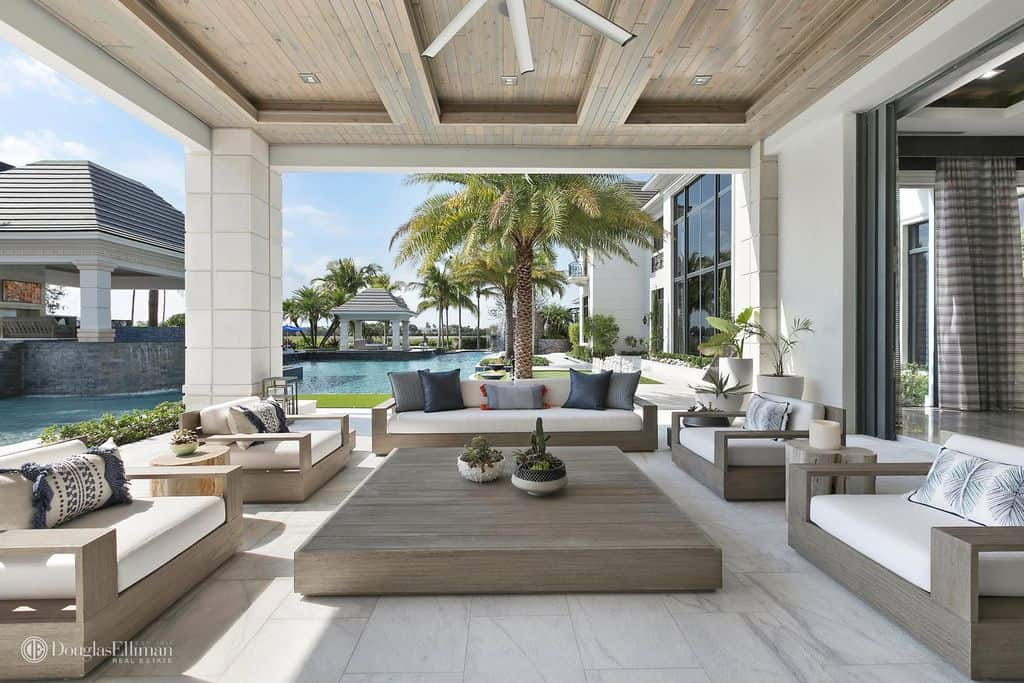 Spacious covered patio next to swimming pool with comfortable patio lounge furniture