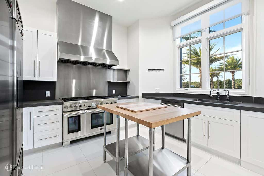 White modern kitchen with stainless steel appliances and backsplash flanked by black backsplashes and countertops, windows, and a small stainless steel table kitchen island with wheels and wood surface standing on white tile flooring.