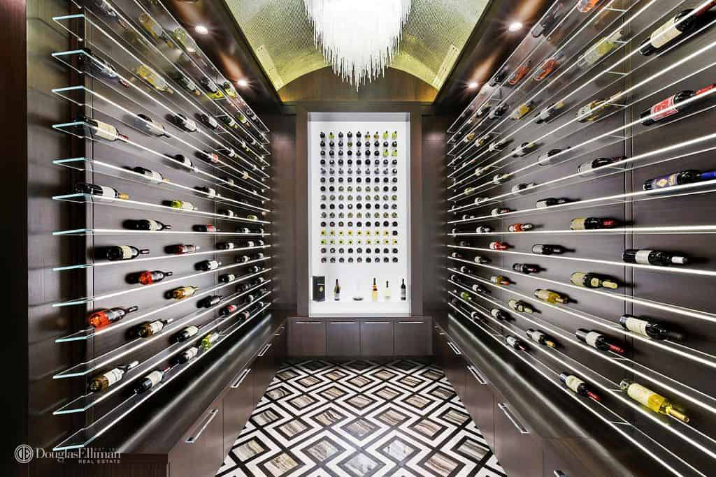 A striking wine cellar fitted with dark wood cabinets and glass shelves over an eye-catching diamond patterned floor. It has a barrel vault ceiling accented by a glam chandelier.