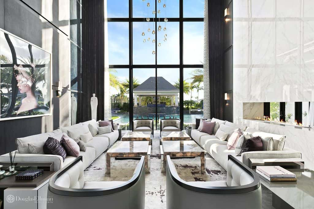 View of luxury living room in modern glam style with huge two-story window.