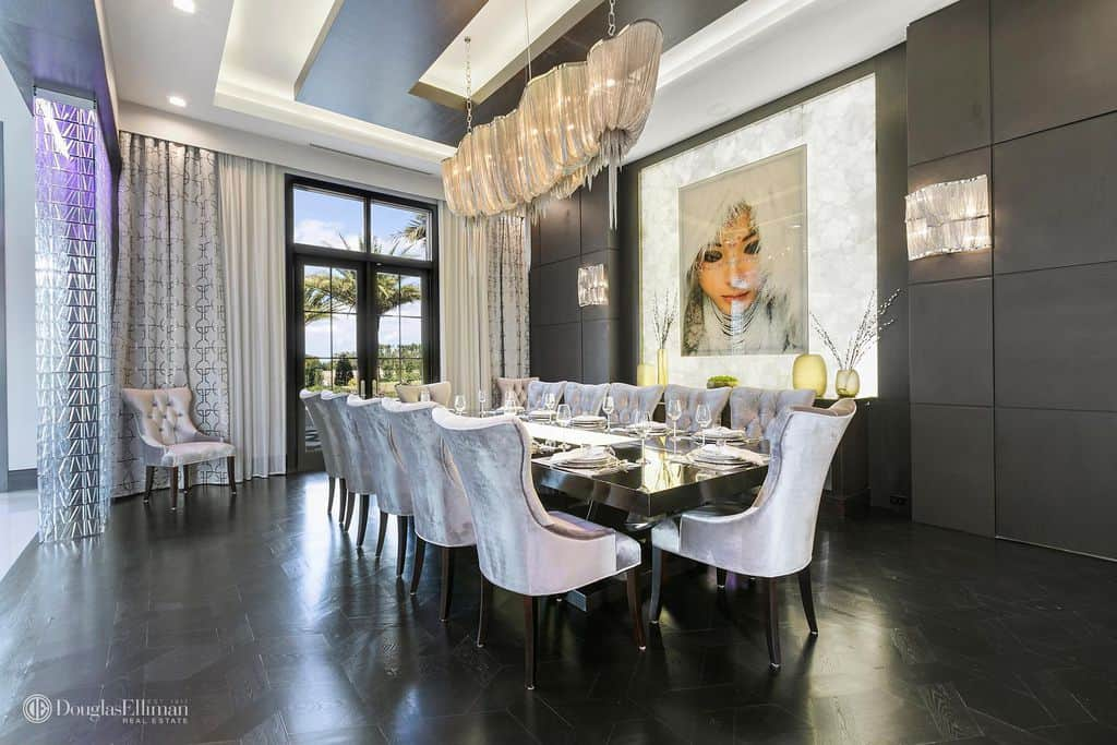 Gorgeous portrait along with an eccentric chandelier creates an interesting tone in this dining room with a long black table and tufted wingback chairs in gray velvet. Dark walls and flooring are balanced with natural light flowing in from the full height glazing