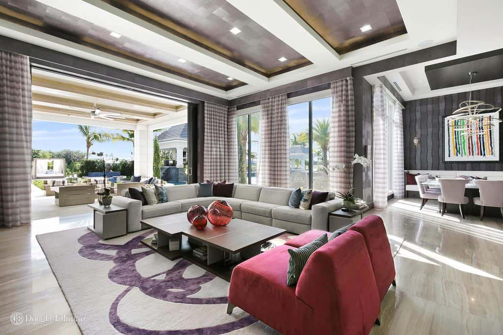 A very stylish home featuring a living room with an L-shape sofa set, two red velvet chairs and a stylish center table set on a classy rug.