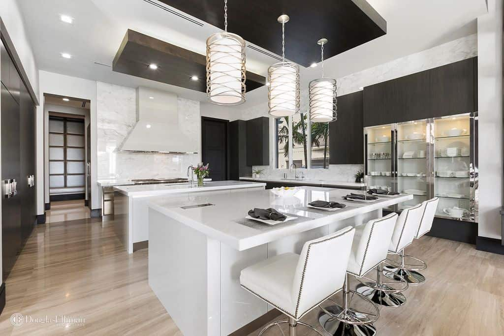 Large modern white kitchen with pendant lights over large island and breakfast bar.