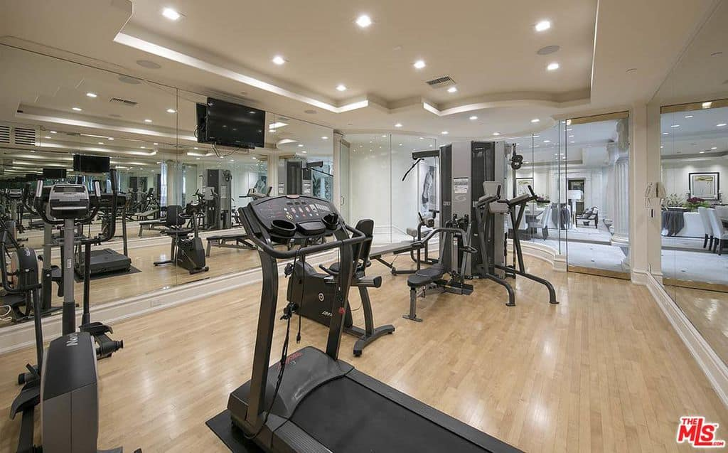 The home gym offer many workout machines on a carpet flooring with a hanging tv
